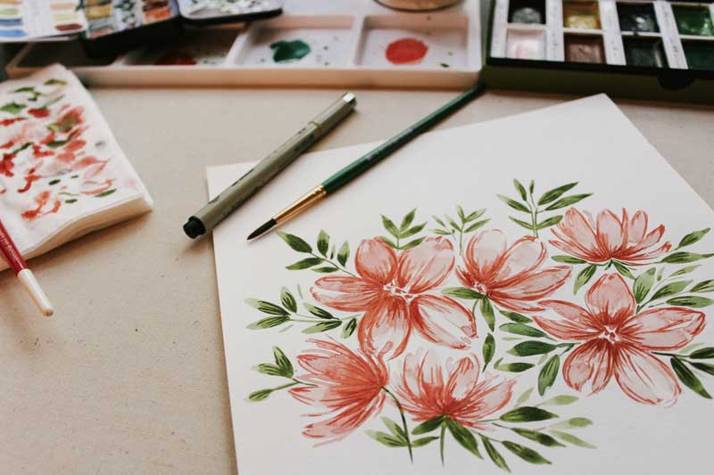 Painting of flowers with art supplies on the desk above it